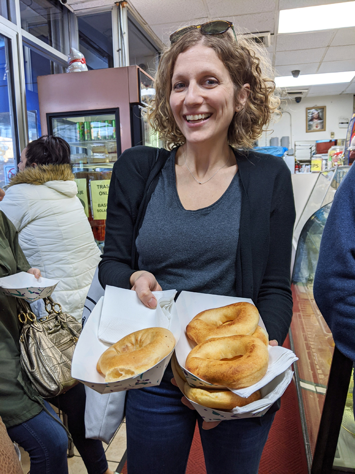A female food tour guide in Queens holds Colombian almojabana.