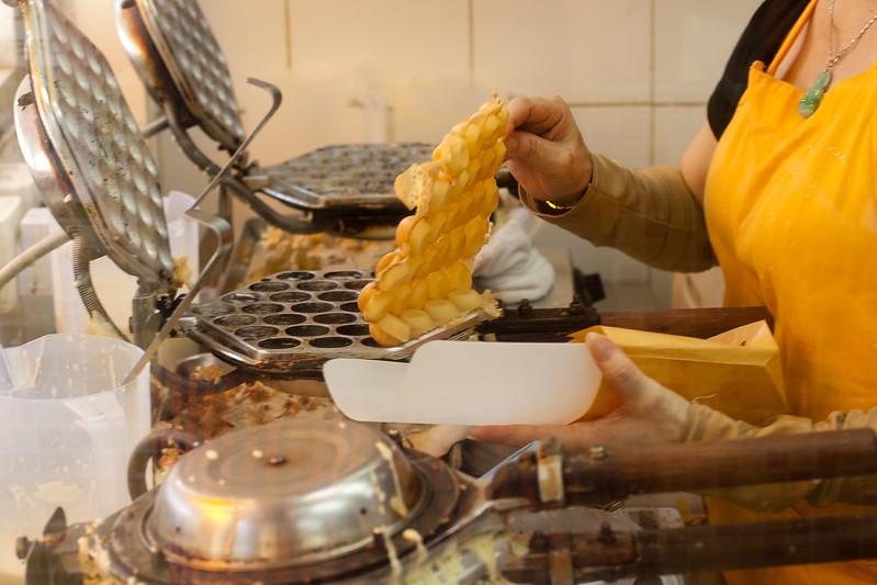 Woman making egg waffles at Mammy Pancake in Hong Kong