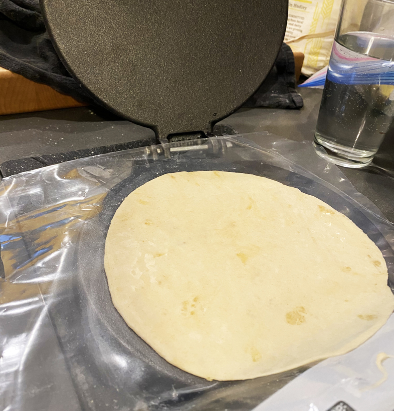 Tortilla press in use with flattened dough