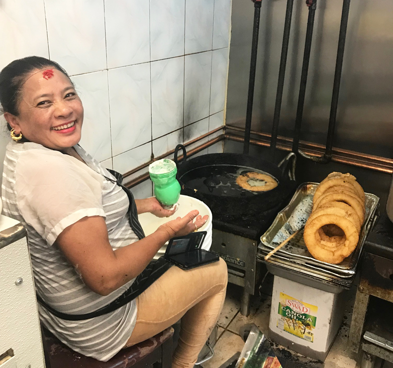 Nepali woman cooking sel roti in Queens restaurant