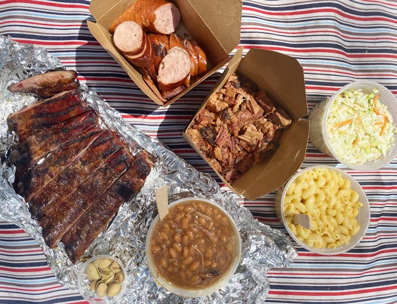 Picnic spread of home-smoked ribs, brisket burnt ends, double-smoked kielbasa, baked beans, mac and cheese and more from home kitchen Queens Custom Barbecue.