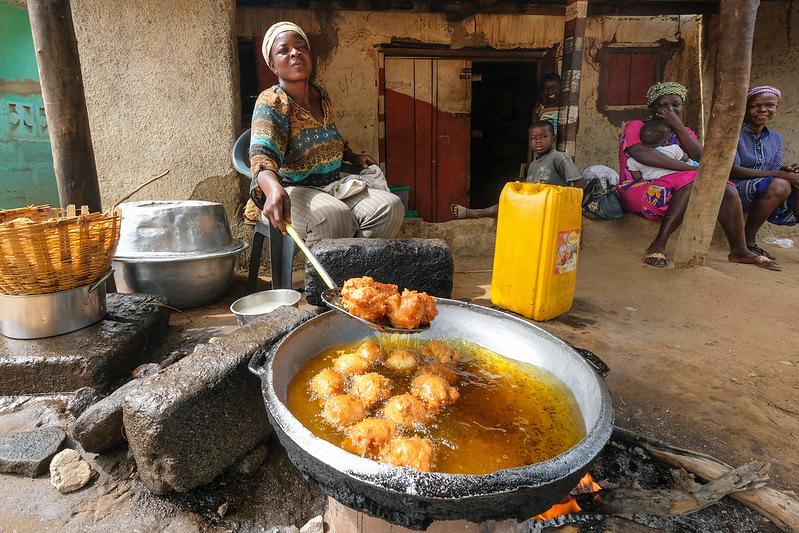 A street food vendor in Ghana fries dough in a big vat of oil.
