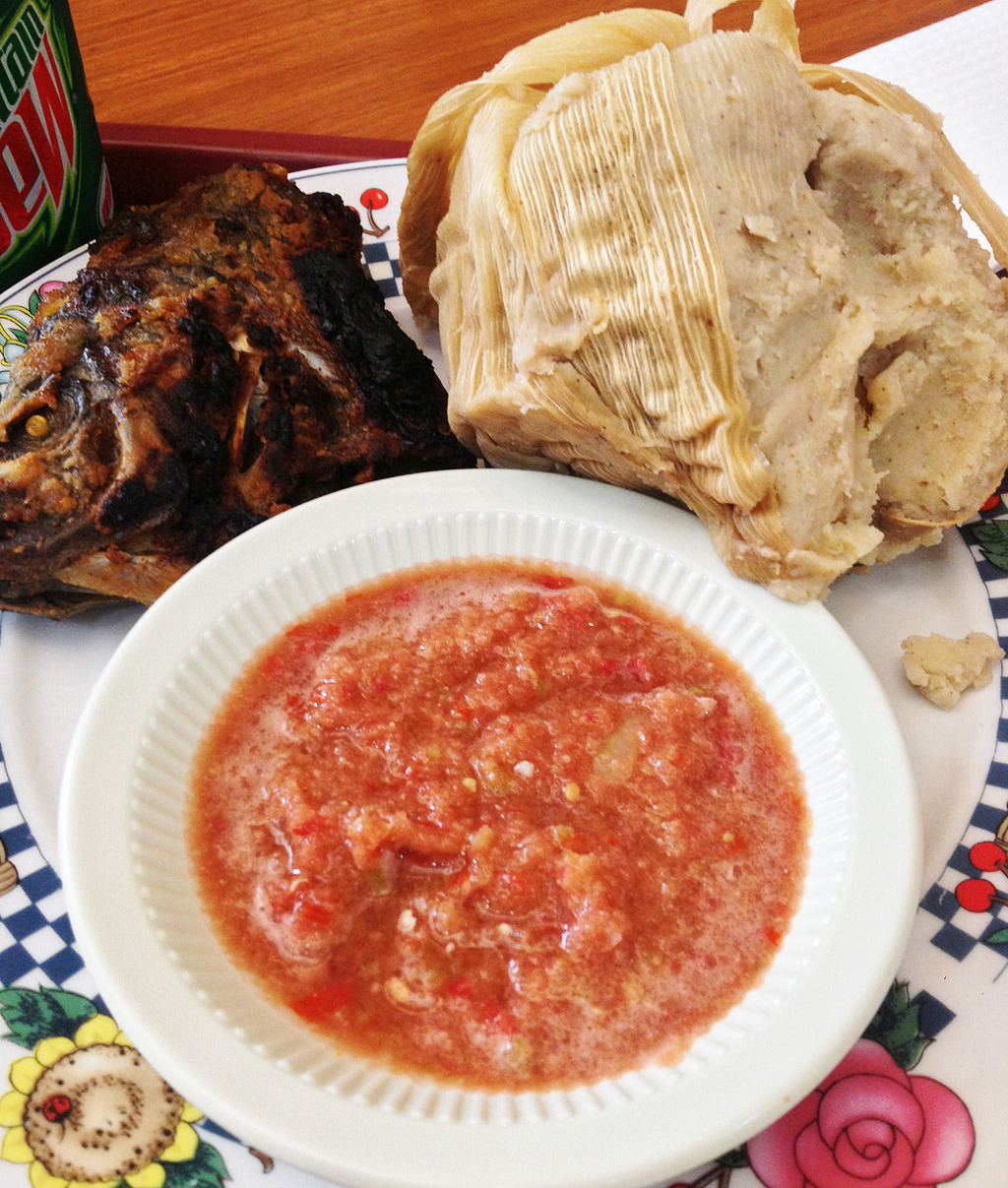 Kenkey is a sour mash made from corn, typically served with fried fish and pepper sauce in a typical Ghanaian meal.