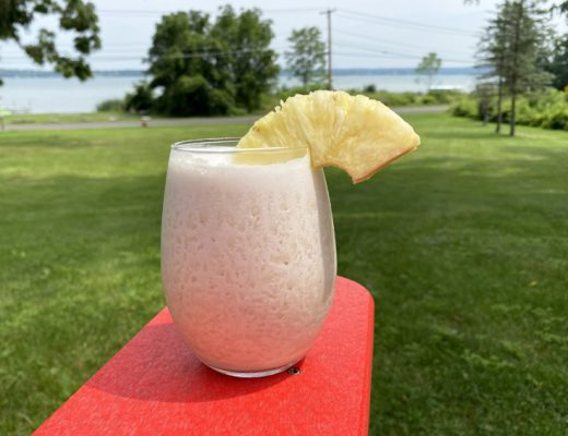 The Dirty Banana tropical cocktail pictured in front of Cayuga Lake in New York.