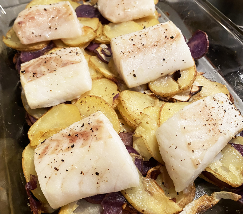 Wild-caught Pacific cod from a Good Chop delivery box is seasoned and placed over sliced potatoes to be roasted