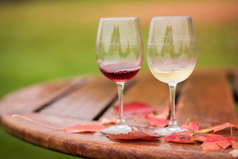 Two wine glasses over autumnal leaves at a past Bethel Woods Center for the Arts wine festival, in the Sullivan Catskills region of NY state