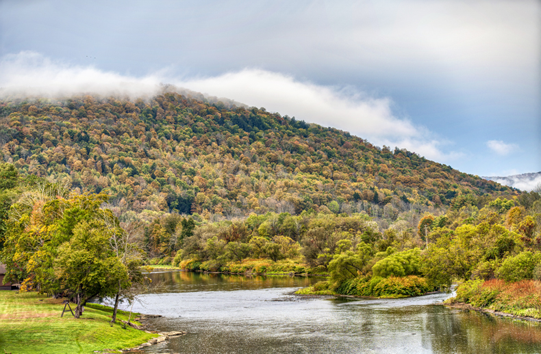 A fall shot of the beautiful Delaware River showing a mountain of colorful autumn trees, in New York state's Sullivan Catskills region