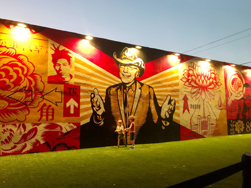 The Shepard Fairey mural at the Wynwood Walls with two kids playing in front of it.
