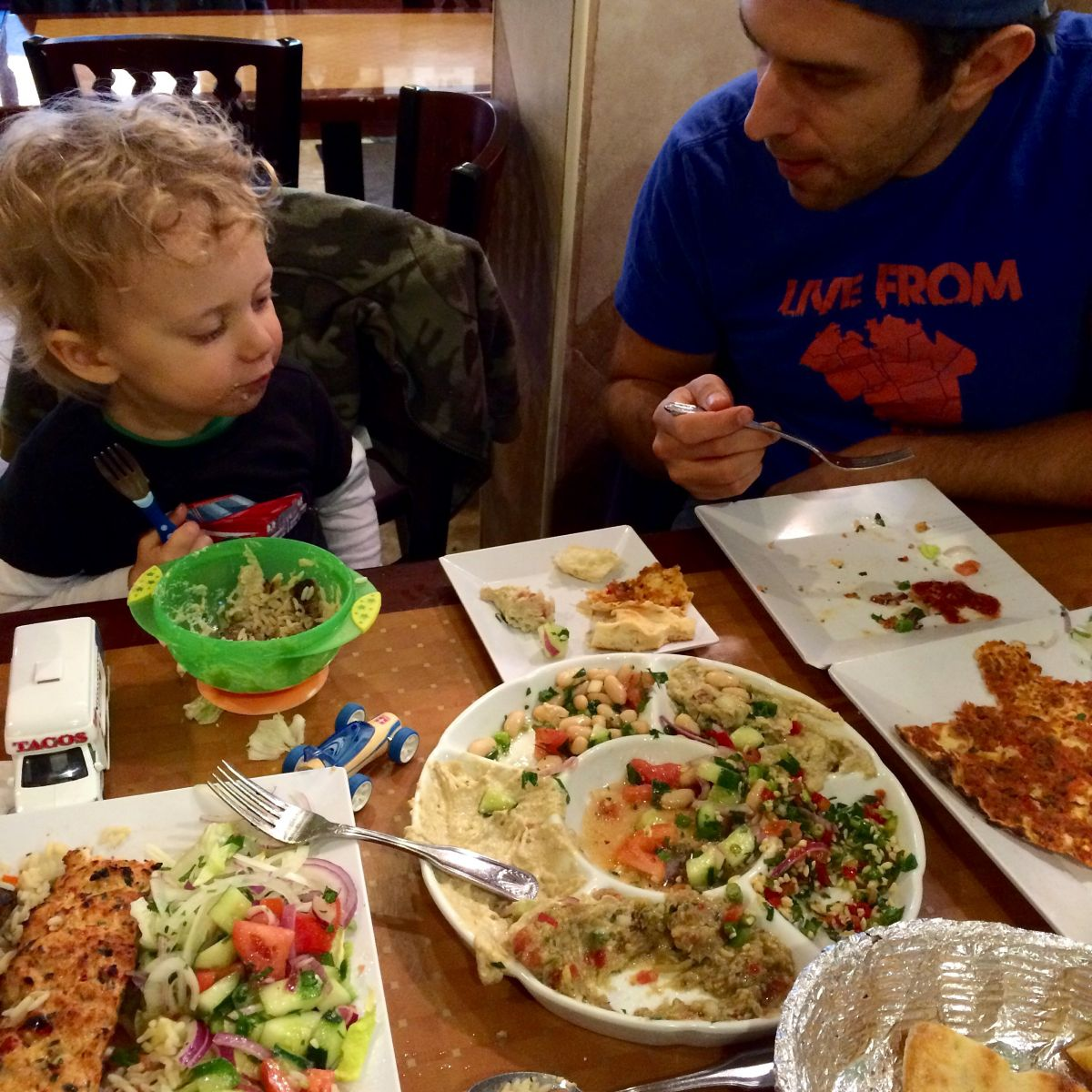 Toddler and dad eating Turkish food at a restaurant