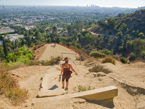 Hiker at Runyon Canyon Park, with a view of downtown Los Angeles
