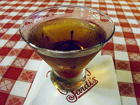 A classic Manhattan cocktail on a red-checkered tablecloth at Sardi's in NYC