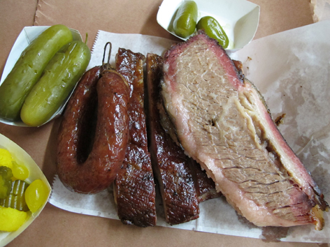 Central Texas BBQ on butcher paper: sausage, ribs, brisket, pickles.