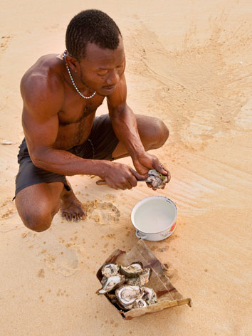 Villager shucks local oysters at Bureh Beach, Sierra Leone