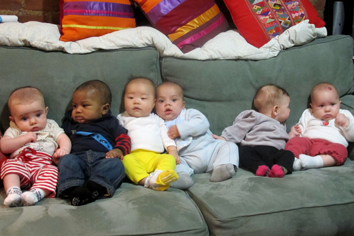 Babies lined up on a couch