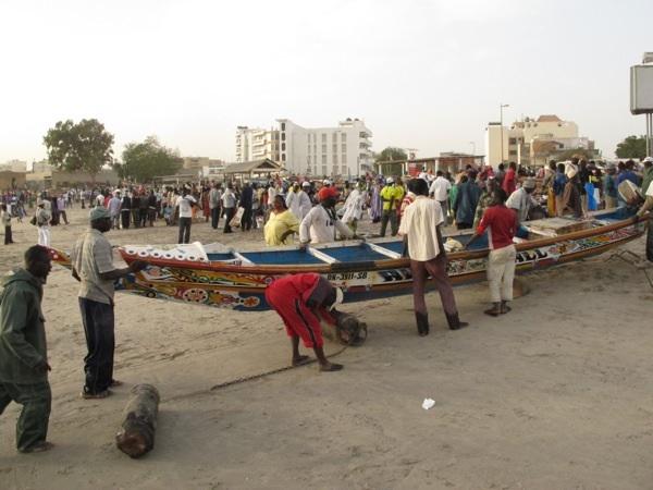 Men with pirogues at Dakar's Soumbedioune Market.