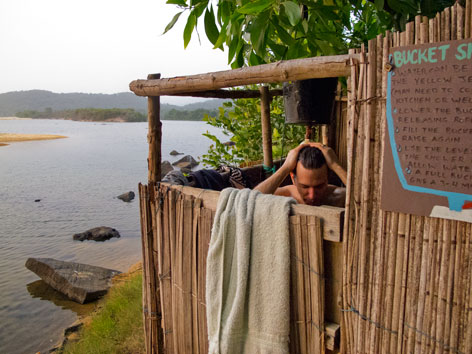 Tribewanted guest using bucket shower, Sierra Leone