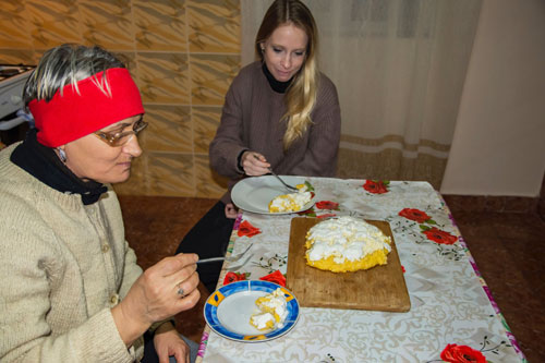 Two women sitting down at a table to eat mamaliga with cheese and sour cream in rural Romania.