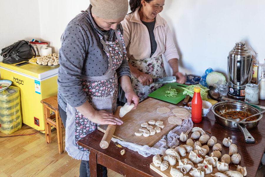 Rural Mongolian women cooking at a camp in the countryside of Mongolia.