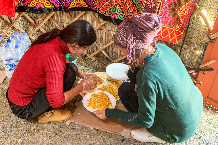 Kazakh women preparing food on the ground in western Mongolia.
