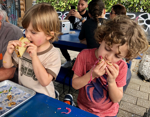 Two little boys eating tacos in Wynwood, Miami, Florida.