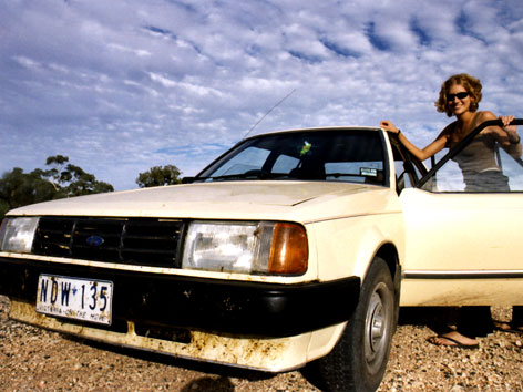 Woman with car in Australian outback
