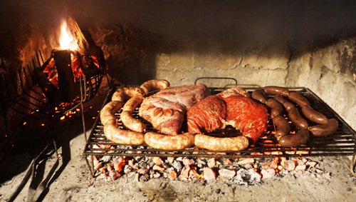 Traditional asada over wood-burning fire in Mendoza, Argentina