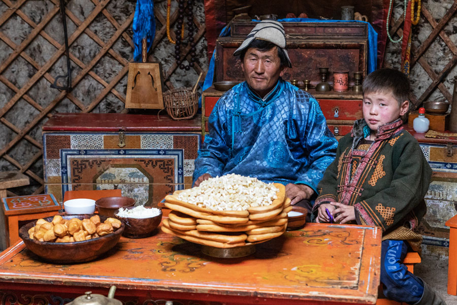 Mongolian man and child behind a table of Mongolian foods, ready to share with travelers.