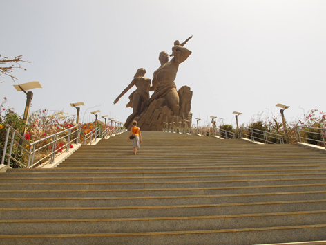 Female tourist climbs the stairs to Dakar's African Renaissance Monument, Senegal