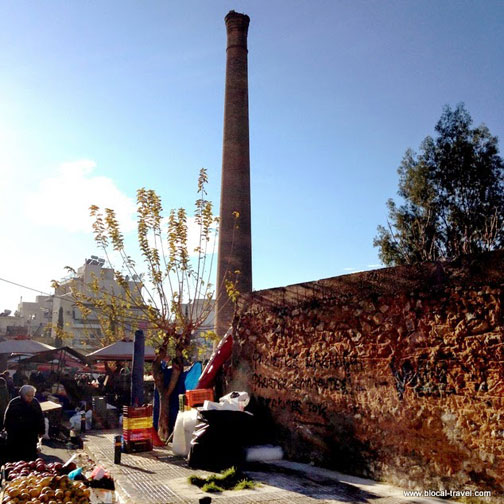 Perissos farmers market in Athens, Greece, with abandoned chimney in background