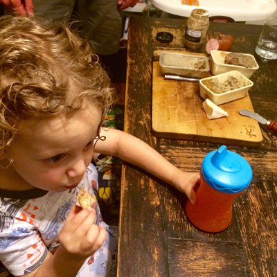 Toddler boy eating charcuterie.