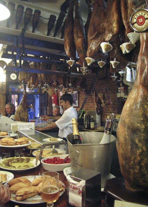 Legs of ham hanging above a pintxos bar in San Sebastian, Spain