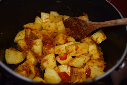 Chopped potatoes cooking in a Pakistani curry at home