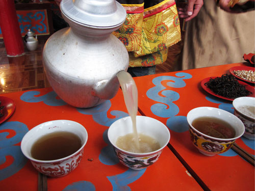 Pouring yak butter tea from a kettle in Tibet.