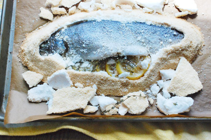 Sea bass baked in a salt crust, shown during preparation