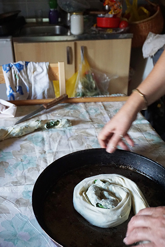 Spriling the burek, or pita, dough into a pan, at a cooking class in Bosnia.