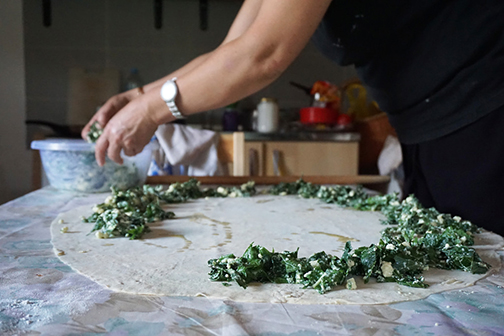 Spreading a mixture of greens and cheese on top of rolled-out burek dough for pita in Bosnia.