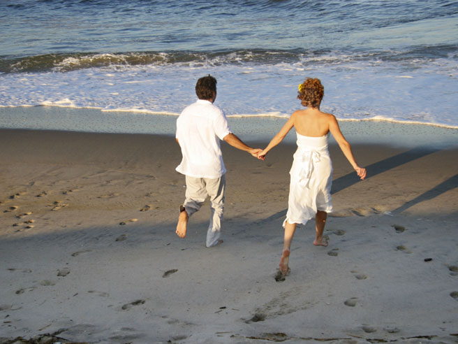 Couple runs toward beach in wedding clothes, Jersey Shore