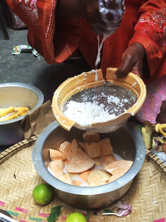 Woman grating coconuts to make a sweet potato dessert in Zanzibar