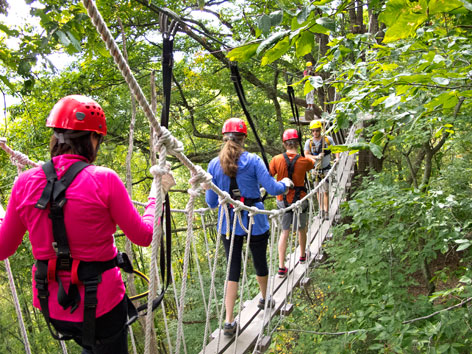 Participants cross a rope bridge on the Navitat Canopy zipline course, Asheville