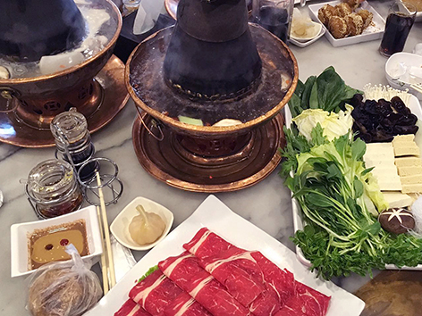 Beijing-style hot pot, or shuan rou, using a miniature coal-burning stove with chimney.