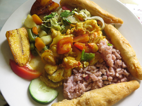 A plate of curried lobster with rice and peas, plantains, and festival on Winnifred Beach in Portland, Jamaica