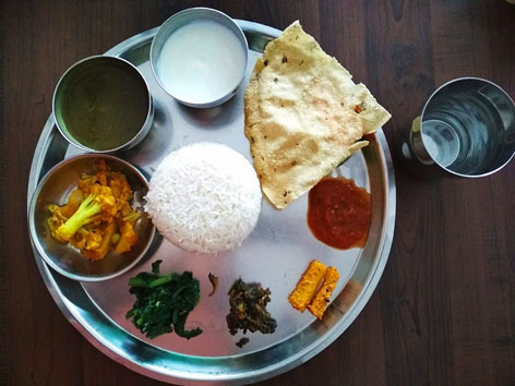 Dal bhat, a thali-style dish in Kathmandu, Nepal, that places lentil dal, a curry, pickles, and a papad around a mound of rice.