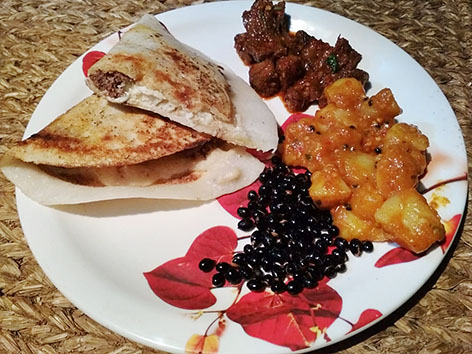 A plate of chatamari, Nepali crepe, with some sides of beans, potatoes, and meat from Kathmandu.
