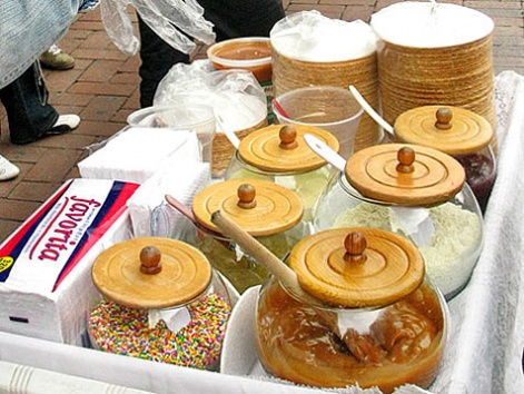 A street cart with jars of toppings for fresh obleas on the street in Bogota.