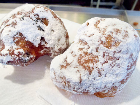 An olliebollen and a krentenbollen purchased on the street in Amsterdam, the Netherlands