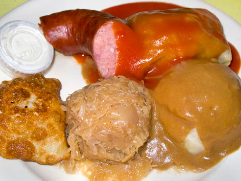 A plate of Polish food with stuffed cabbalge, pierogi, kielbasa and more form Polish Village Cafe in Detroit.